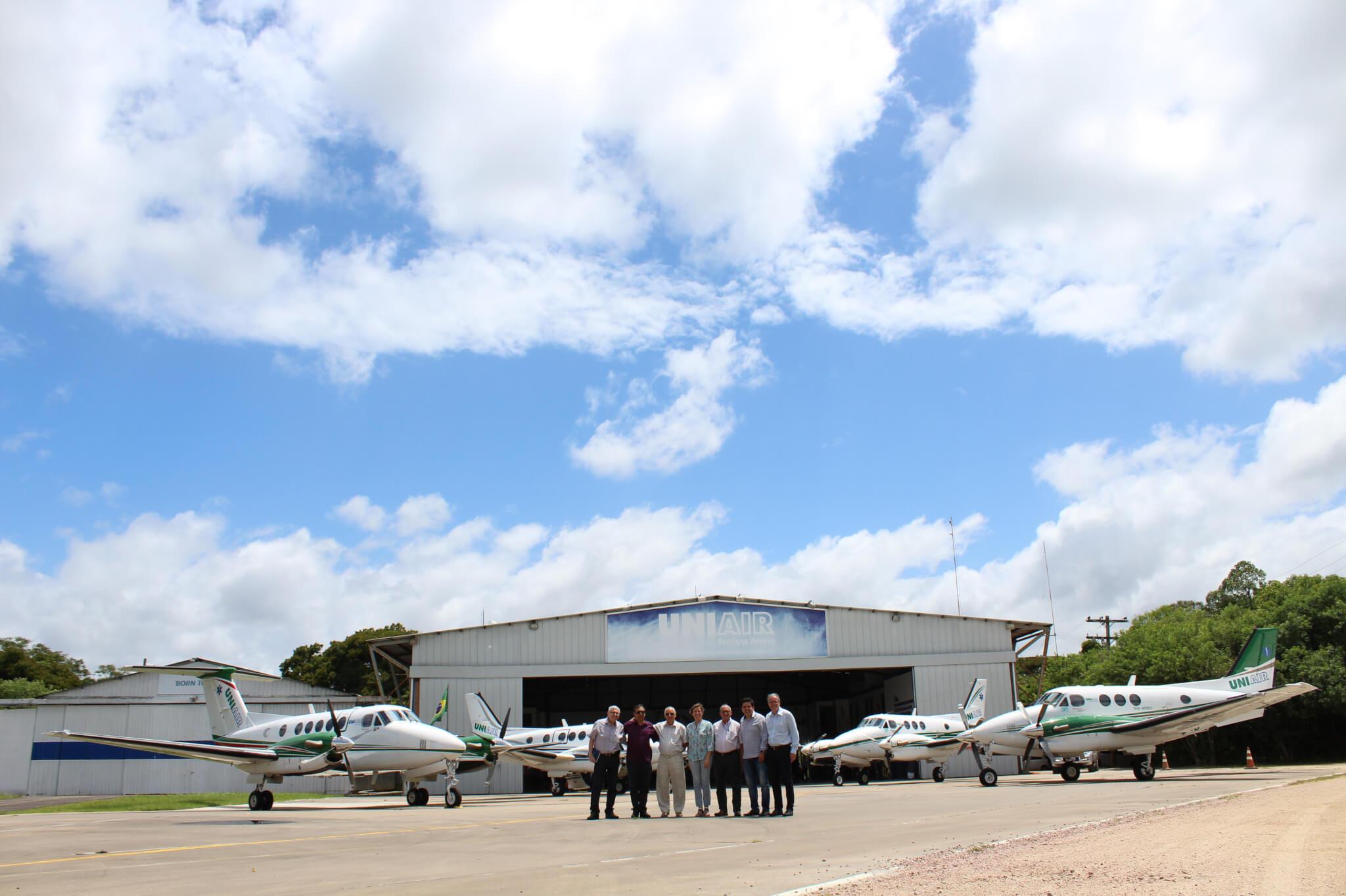 Conselheiros e diretores no hangar, à frente da frota de aeronaves: Ilson Enk, Evando Reis, Nilson Luiz May, Liliane Centeno, Maurício Goldbaum, Luis Carlos Cavalheiro e Ronaldo Mattia